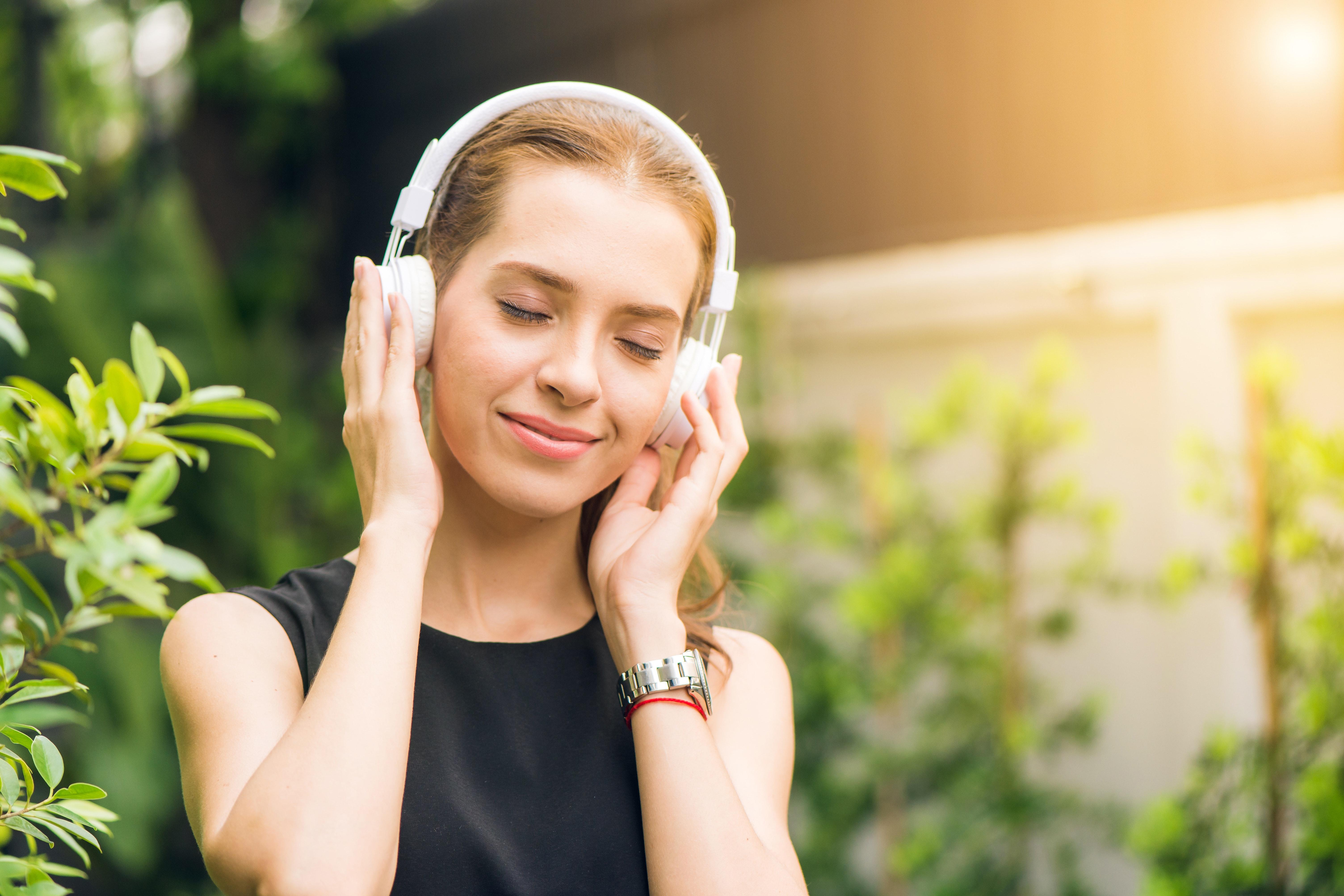 woman-wearing-black-sleeveless-dress-holding-white-headphone